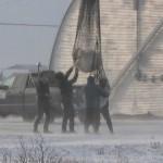 Een verdoofde ijsbeer komt van de grond, opgetild door een helikopter in het Canadese Churchill.