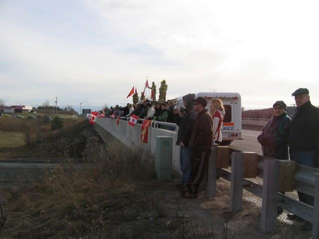 Canadezen wachten op een viaduct over snelweg 401 in Ontario op een rouwstoet met militairen die zijn gesneuveld in Afghanistan.