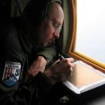 IJswaarnemer Lee Brittle van de Internationale IJspatrouille zoekt naar ijsbergen boven de Atlantische Oceaan.