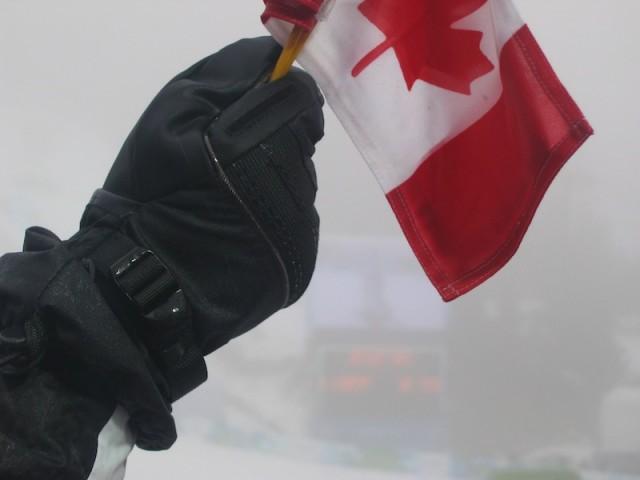 Een toeschouwer zwaait met een Canadees vlaggetje tijdens de Winterspelen.