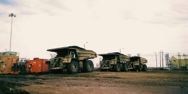 Giant dump trucks are used in the extraction process of bitumen from open pit mines.