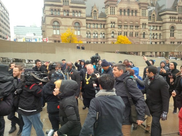 Burgemeester Rob Ford van Toronto wordt achtervolgd door een horde journalisten en cameralieden bij het stadhuis.