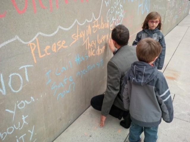 Ed Zwolinski tekent zijn protest aan in krijt op een muur bij het stadhuis van Toronto.