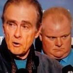 Plaatsvervangend burgemeester Norm Kelly van Toronto voert het woord over de bestrijding van de stroomuitval in de stad als gevolg van zware ijzel, met burgemeester Rob Ford op de achtergrond.