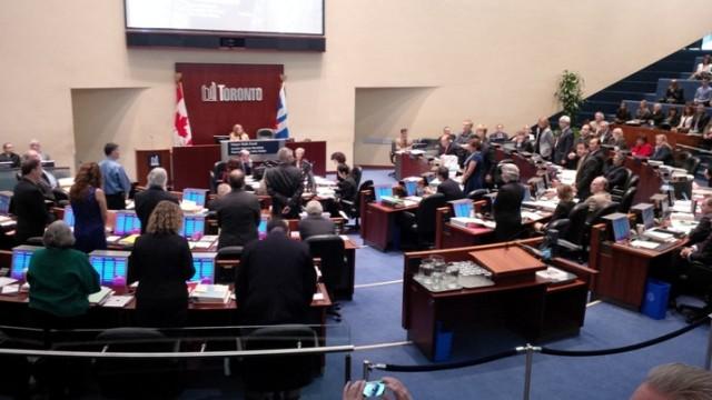 Raadsleden die burgemeester Ford oproepen enige tijd vrij te nemen gaan staan in de raadszaal van Toronto.