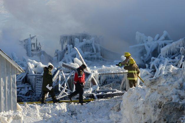 Reddingswerkers bij het in de as gelegde bejaardenhuis, la Résidence du Havre. Foto AFP