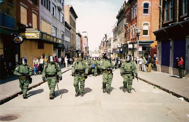 Agenten van de mobiele eenheid lopen door een winkelstraat in Québec-Stad. Er is veel politie bij de Summit of the Americas.