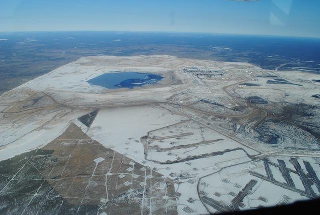 Teerzandmijn vanuit de lucht gezien, met open putten (rechts) en afvalwater (boven).