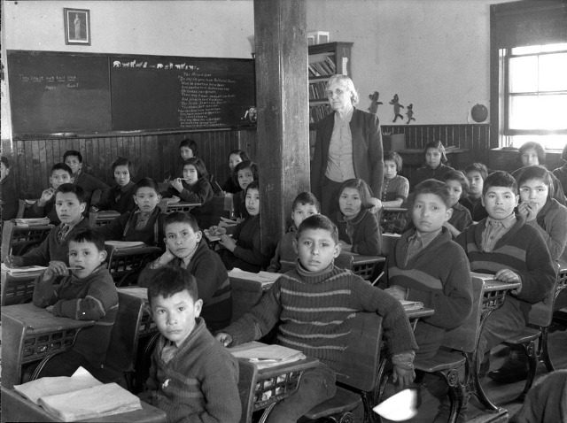 "Cree students at the Anglican-run Lac la Ronge Mission School in Saskatchewan in 1945. The blackboard on the left reads: ""Thou Shalt Not Tell Lies."" Archives and Library of Canada"