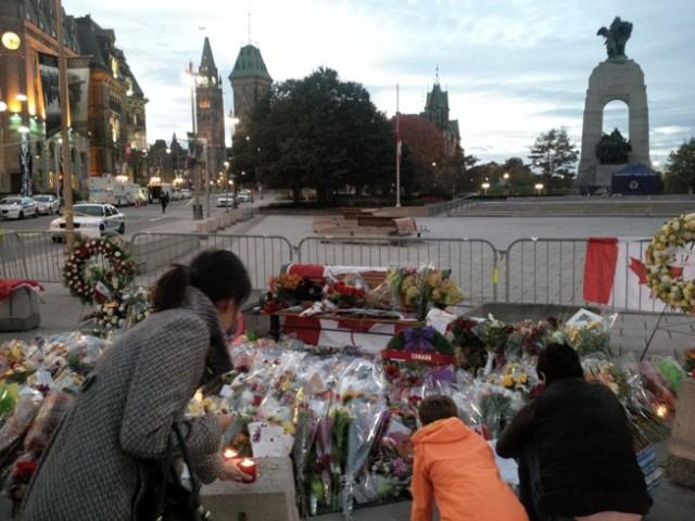 Mensen leggen bloemen en plaatsen kaarsjes nabij het nationale oorlogsmonument in de Canadese hoofdstad Ottawa, waar deze week een militair werd doodgeschoten.