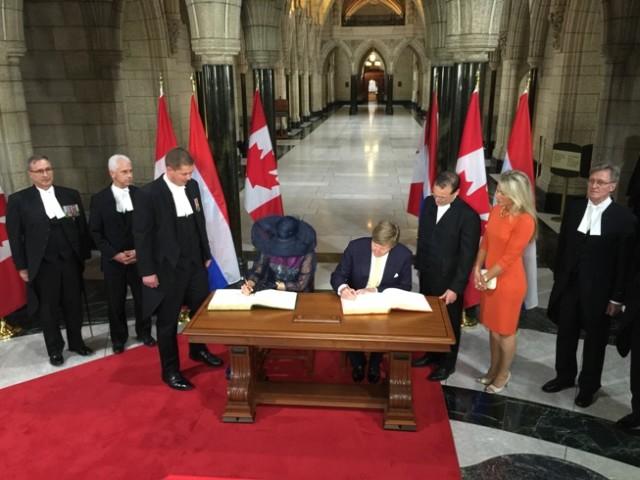 Koning en koningin tekenen het gastenboek van het Canadese parlement in Ottawa.