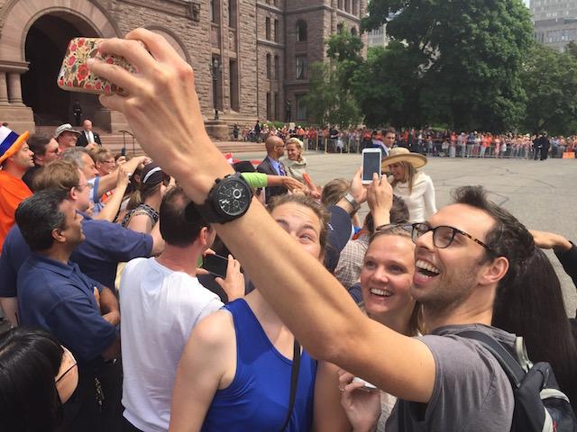Toeschouwers nemen 'selfies' terwijl Koningin Maxima de menigte bij het parlementsgebouw van de provincie Ontario begroet.