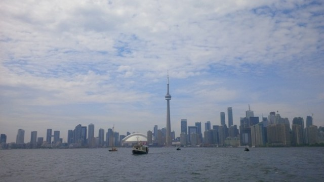 De boot 'Hiawatha' met het koninklijk paar aan boord vaart van het centrum van de stad naar Toronto Island Park.