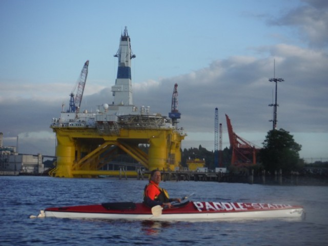Kayaktivist Carlo Voli in his kayak in front of the Polar Pioneer drilling rig in the port of Seattle.