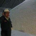 Een werknemer van Potash Corp bij een berg potash of kali, een ingredient van kunstmest.
